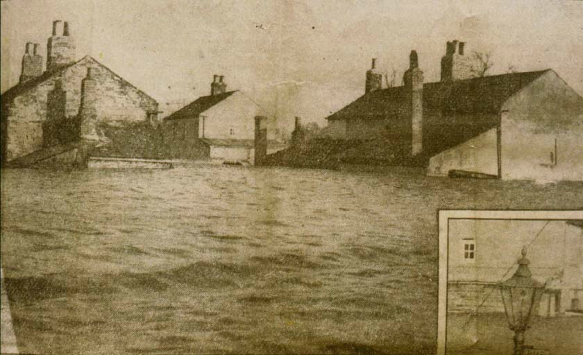 Cottages in Watergate, surrounded by floodwaters.