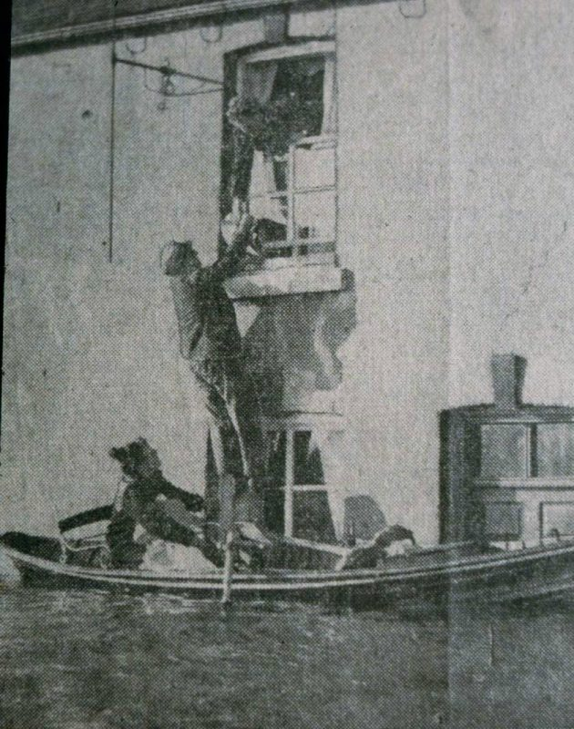 Family rescuing goods by rowing boat from an upstairs window of their home