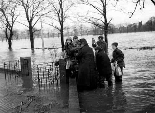 A policeman and George & Michael Wheatley helping Mrs Edith Woolard 1960.